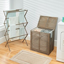 Towels hanging on bamboo collapsable laundry rack, bamboo hamper, gray wall, rug, natural wood floor