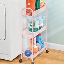 pink rolling trolley cart with detergent, dryer balls, lint roller next to white washing machine