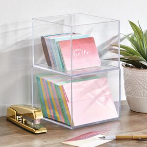 clear stacked bins holding note cards, envelopes, gold stapler, plant on wood shelf, white wall