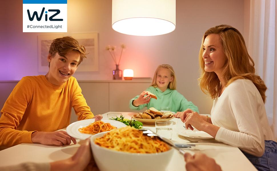 Na foto um jantar em família, com a mãe e seus dois filhos, em um ambiente iluminado com WiZ.