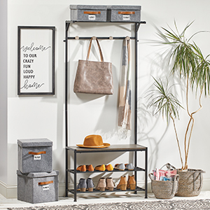 Entryway setting, black cubby with purses, shoes, hat, gray storage cubes, woven basket with plant