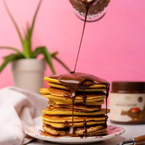 ChocZero Chocolate Hazelnut Spread drizzled on a stack of pancakes.