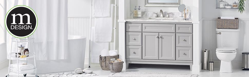 White bathroom setting with tub, shower curtain, gray sink vanity and toilet with mDesign logo