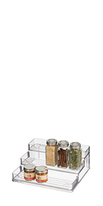Small clear plastic 3-tier stadium spice rack pantry organizer with glass jars on white background