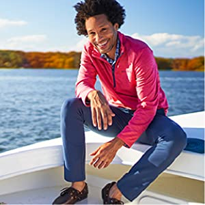 Man wearing vineyard vines pants, plaid button up, and red pullover sitting on a boat.
