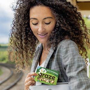 Een vrouw op straat eet van een punnet van graze notensnack mix