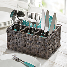 brown woven utensil caddy holding spoons, forks, knives on a white wood table, window in background