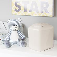 cream mini wastebasket, blanket, blue striped teddy bear on white shelf, gray wall, star