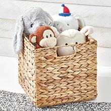natural woven basket on white floor holding stuffed toy monkey, elephant, bunny, bear