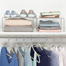 expandable metal racks holding shoes, sweaters on white shelf with clothes hanging below, white wall