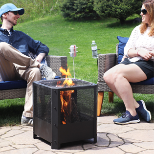 fire pit with fire burning and people relaxing in patio chairs