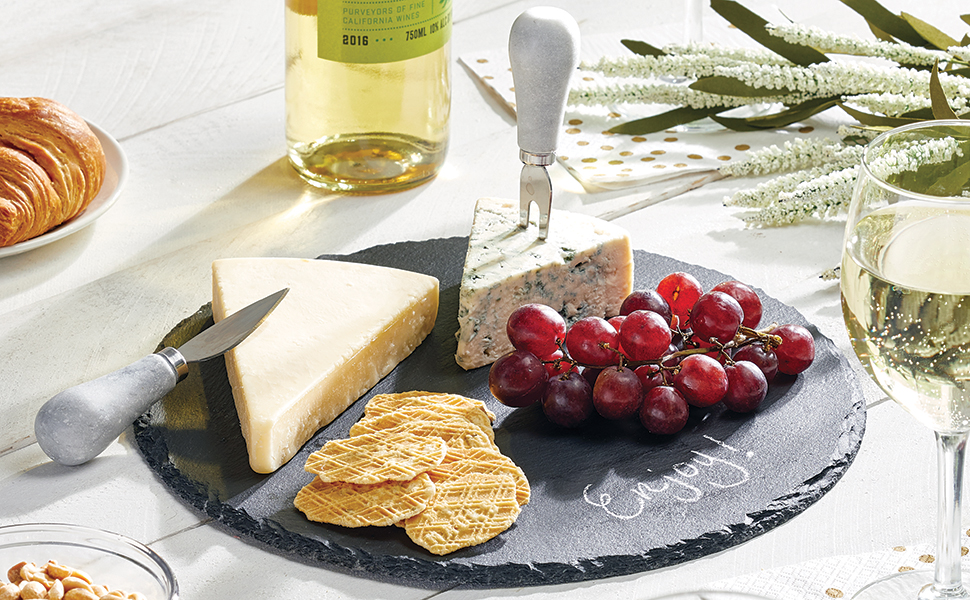 slate stone platter tray holding crackers, grapes, cheese, knives on a white wood table, wine, glass