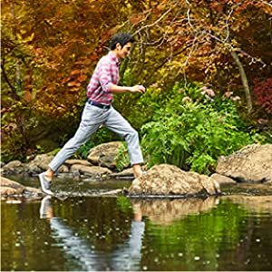 Man wearing vineyard vines shirt and pants hopping on rocks in a creek.