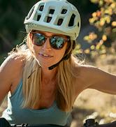 woman mountain biking wearing Zeal Optics Windsor sunglasses