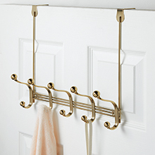 soft brass 5 hook clothing rack holding sweater and strap of purse hanging over back of white door