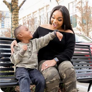 Photo of little boy showing his mom his watch while she smiles.