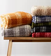 Collection of folded plush throw blankets on bench in assorted colors