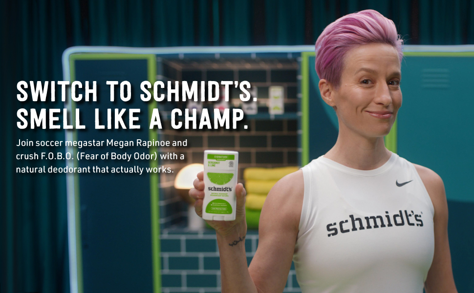 Pink haired girl, smiling while holding a product from the Bergamot and Lime product line