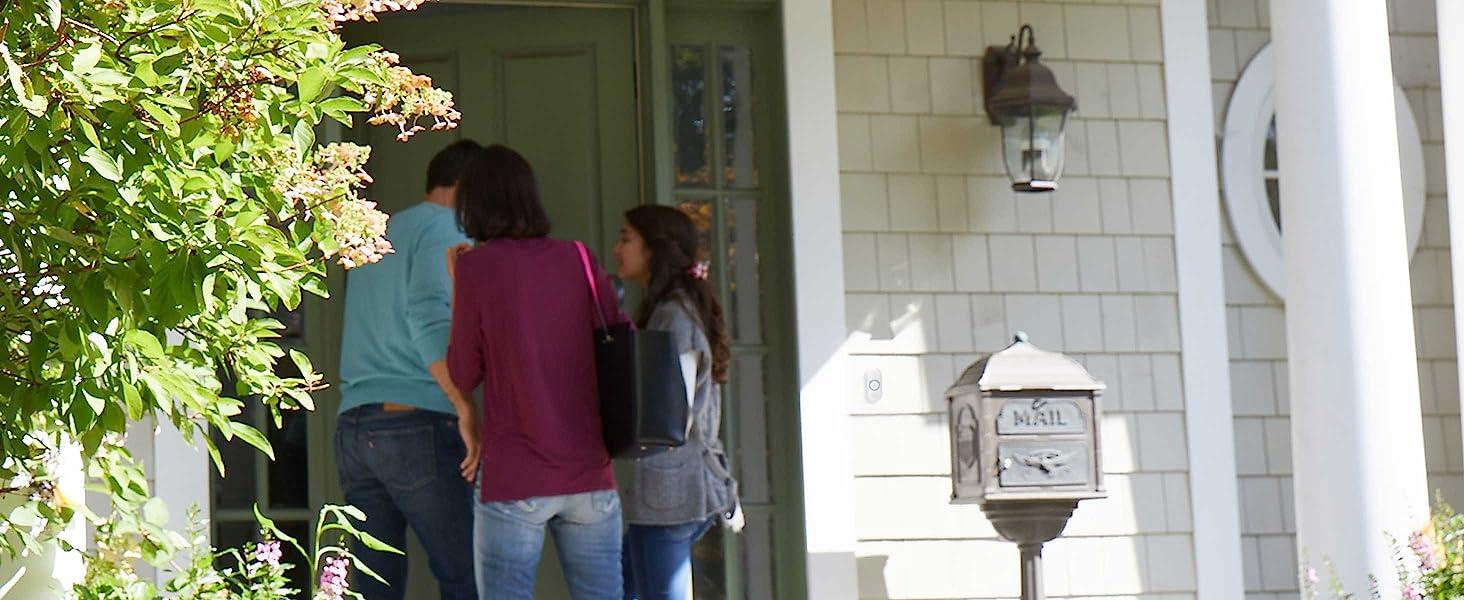 Family entering front door of home, push button doorbell installed to side of door