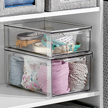 clear bins stacked holding belts and clothing on a white shelf, gray totes on shelf above