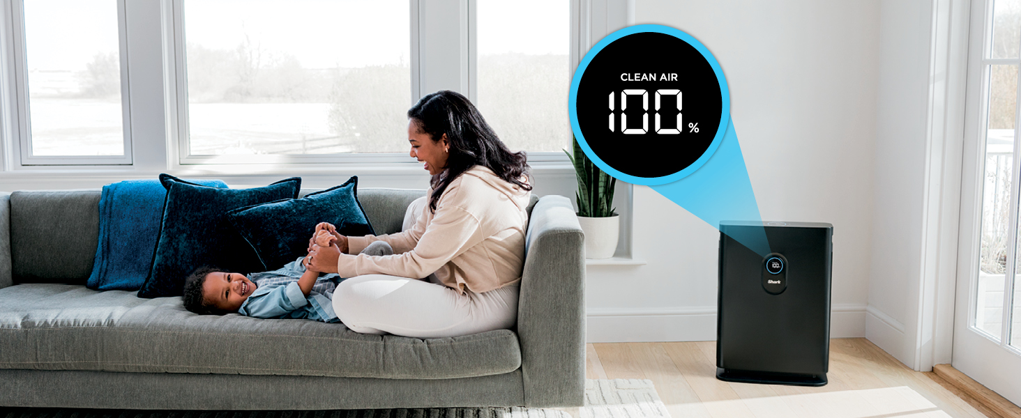 woman playing with her son on the couch while air purifier is at 100