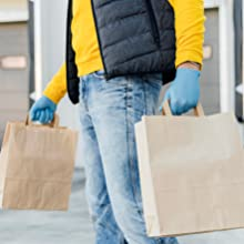 close up delivery man holding paper bags