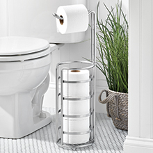 bathroom setting, white toilet, chrome tp holder, plant in basket, gray floor, white walls