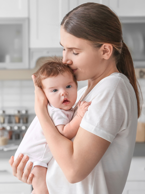 mother holding kissing a baby in her arms dressed white,  kitchen white and wooden furniture