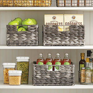 Gray Woven Hyacinth Natural Basket Storage Bins and Clear Canisters on Pantry Shelves with Food