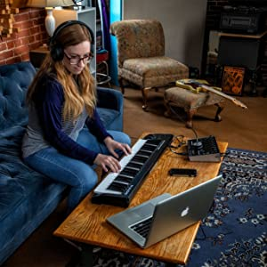 a girl sitting on the couch with headphones on playing on the m-audio Keystation 49 mk 3