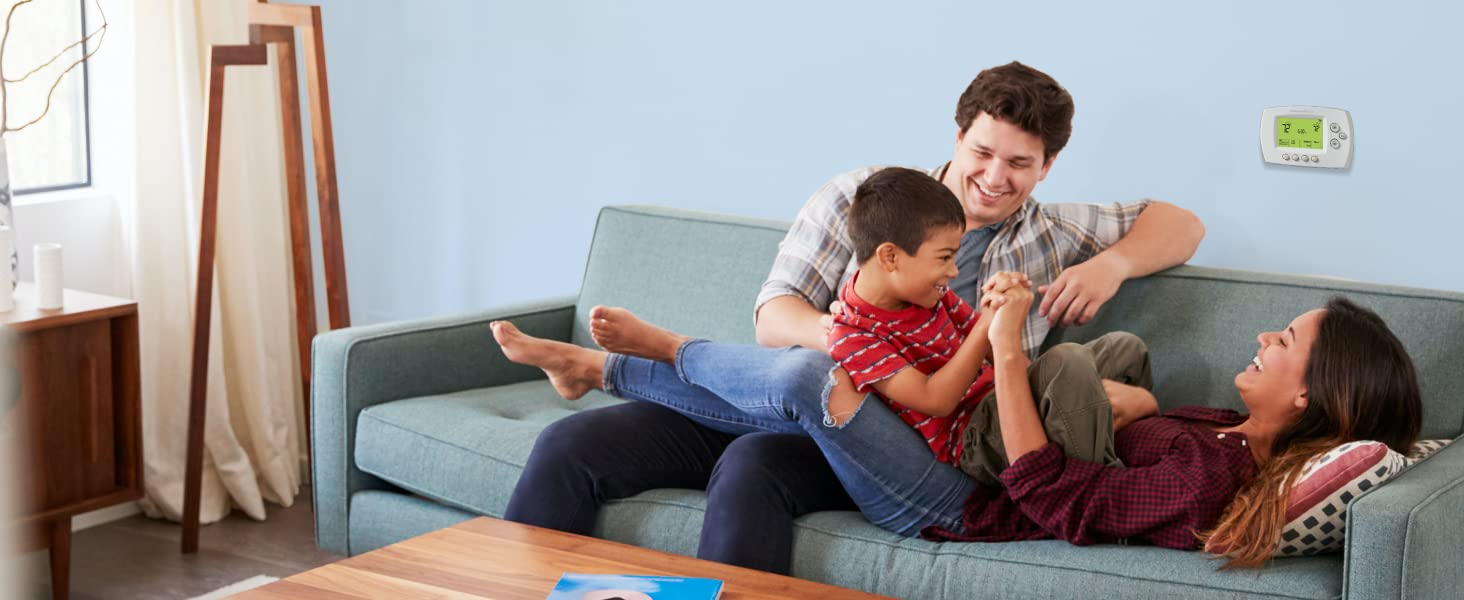 Family playing in front of Wi-Fi 7-Day Programmable Thermostat