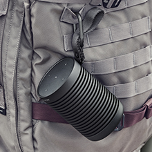Beosound Explore portable speaker hanging on a backpack with the carabiner