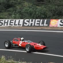 A red race car on a track with a Shell gas station banner behind it.