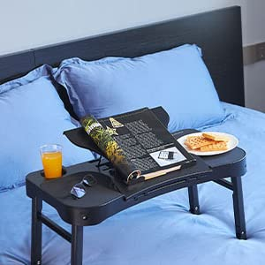 laptop desk with waffle, juice and magazine on bed