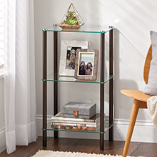 black bookcase with glass shelves holding plant, photos, box, books in white living room setting