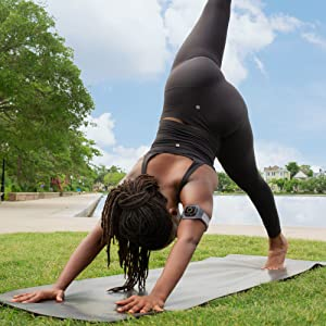 a woman is doing yoga and bending her wrist with actionsleeve on her arm