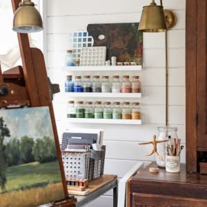 Photo of an art easel with bottles of art supples and paint brushes