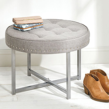round cushioned gray and chrome studded ottoman, 2 wallets, short boots, white wall and floor