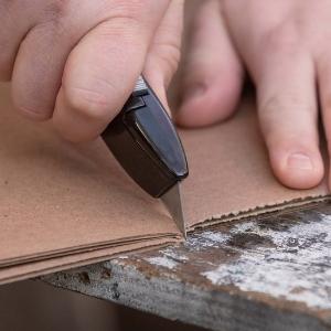 Knife cutting cardboard