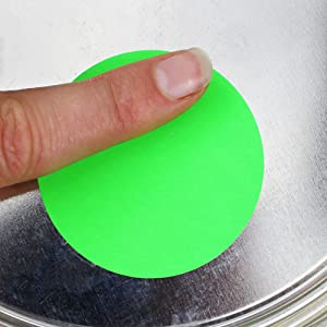 Giant dot sticker being rubbed to adhere to paint can