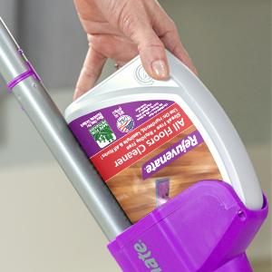 Woman pressing a Rejuvenate All Floors Cleaner bottle into a Click n Clean Multi-Surface Spray Mop