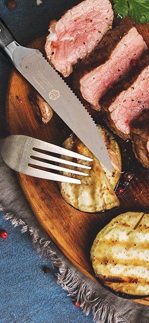 A Kessaku Dynasty Series Steak Knife next to thick ribeye slices and grilled eggplant medallions.