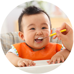 Hand feeding baby with a spoon.