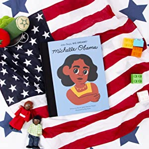 The Michelle Obama book over an American flag with toys around it.
