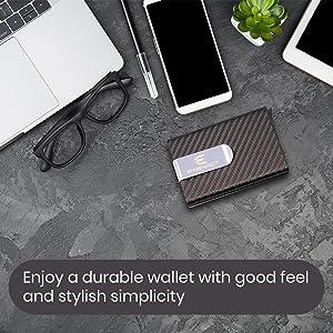 wallet on desk beside laptop, glasses, pen and phone.