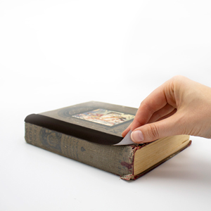 Hand applying black cloth BookGuard tape to old book spine