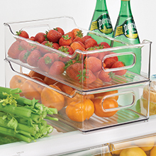 clear stacked bins with handles on fridge shelf holding clementines, strawberries, celery, bottles