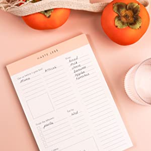 waste less notepad with grocery list on a pink background