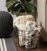 Black round metal bin containing throw blankets in a living room
