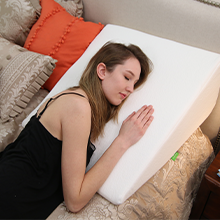 Woman sleeping on the wedge pillow on her side